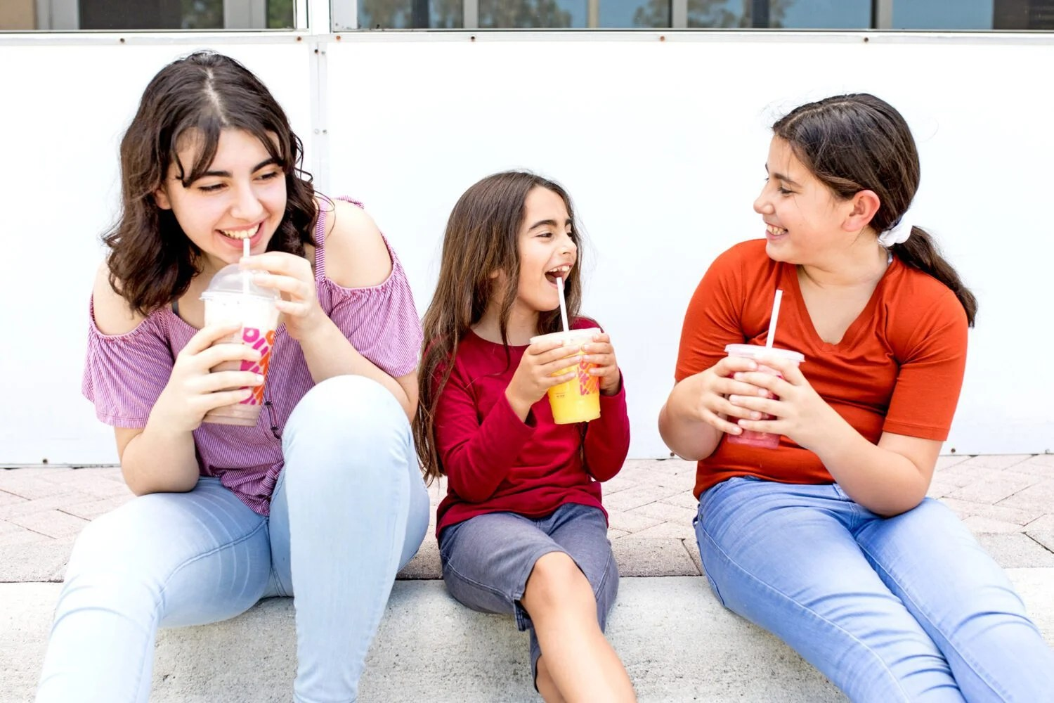 three girls laughing and enjoying a drink from dunkin