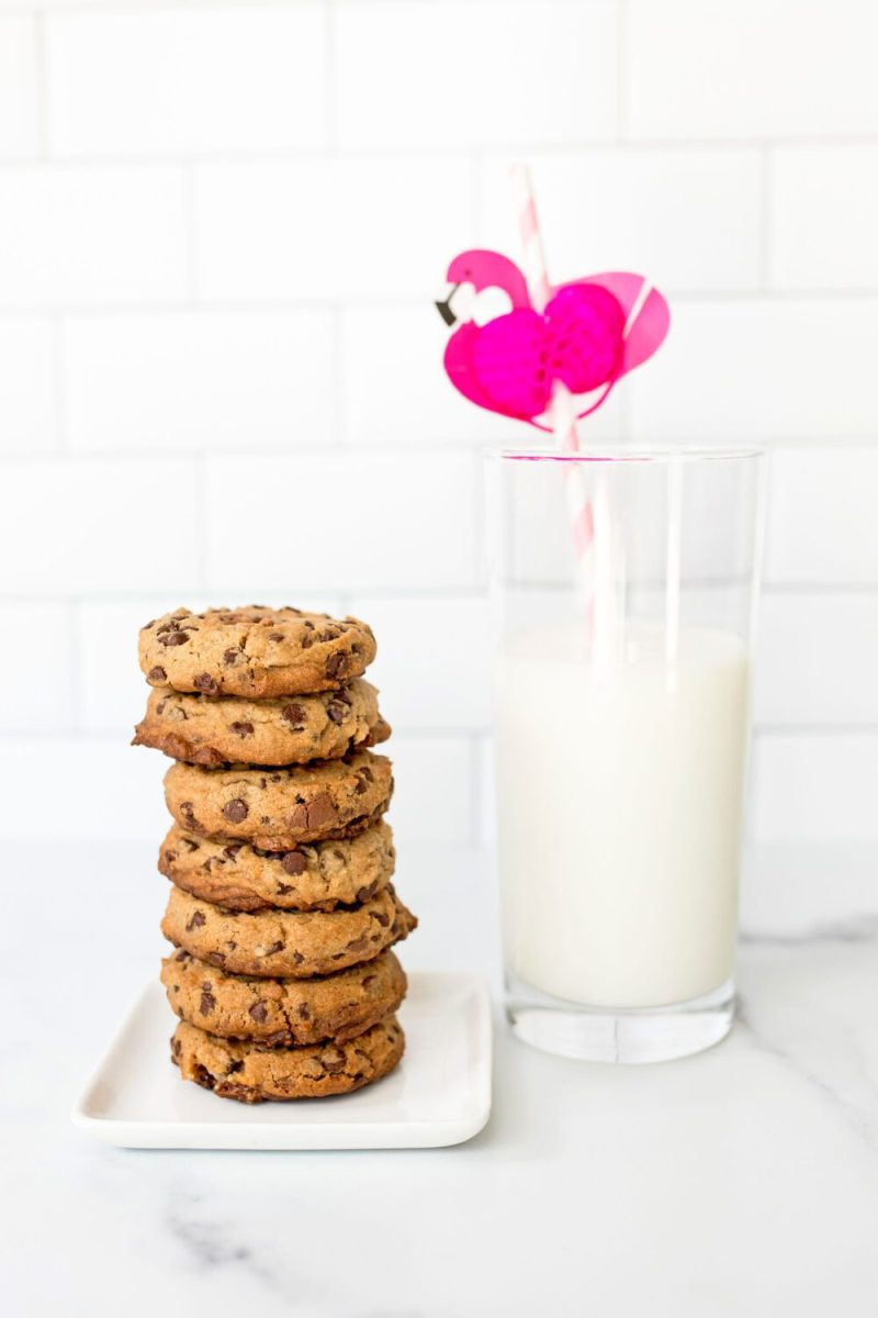 stack of cookies next to a glass of milk with a flamingo straw