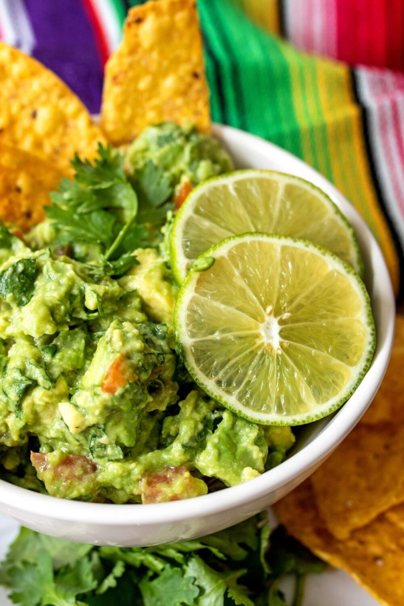bowl of homemade guacamole with slices of lime