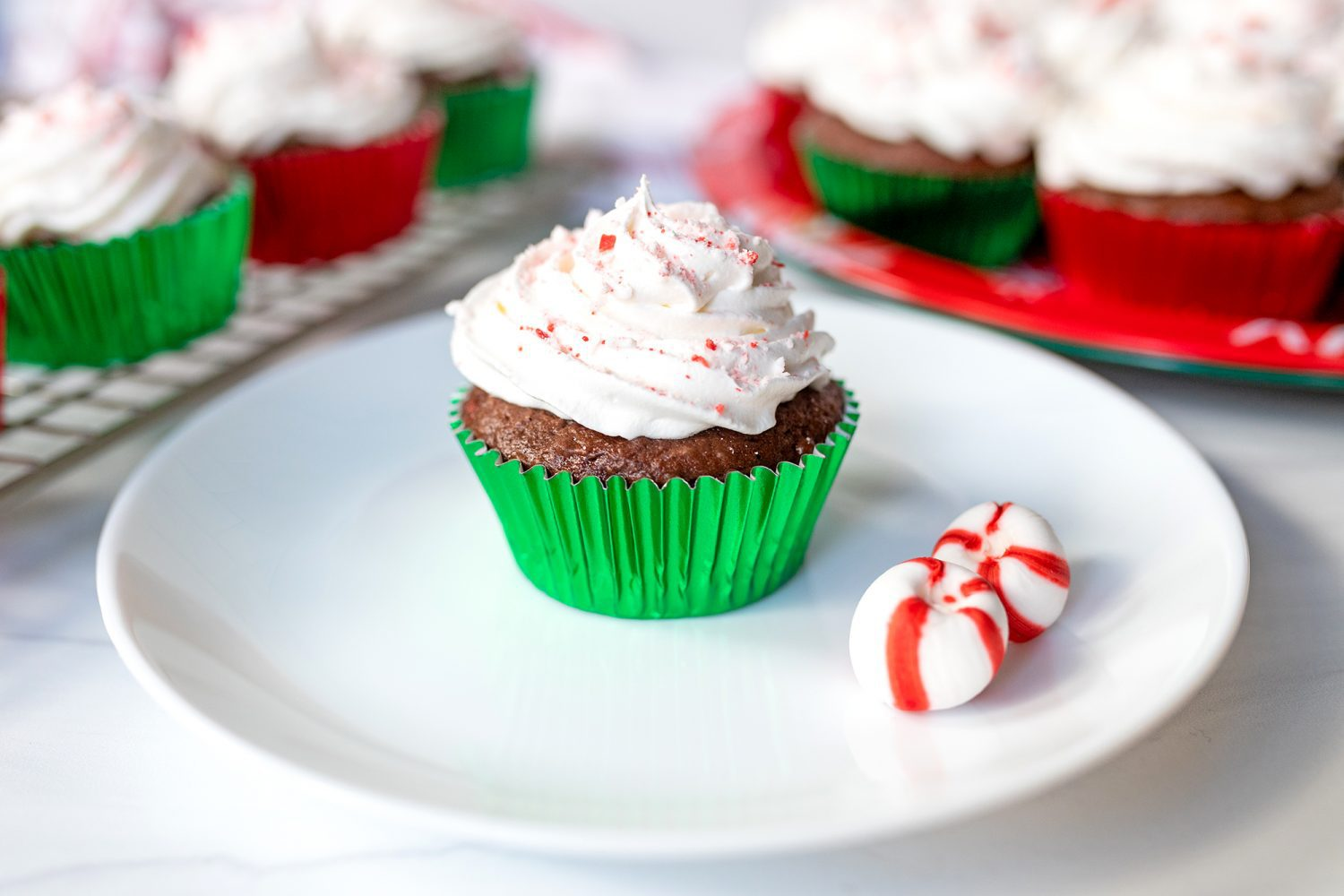 a chocolate peppermint cupcake on a plate with peppermint candies