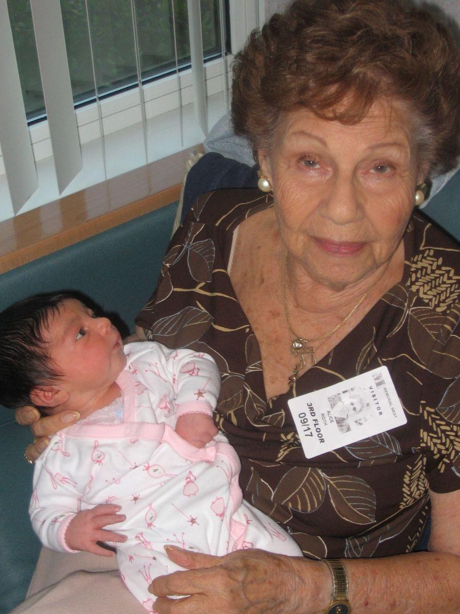 newborn baby looking up at her great grandma
