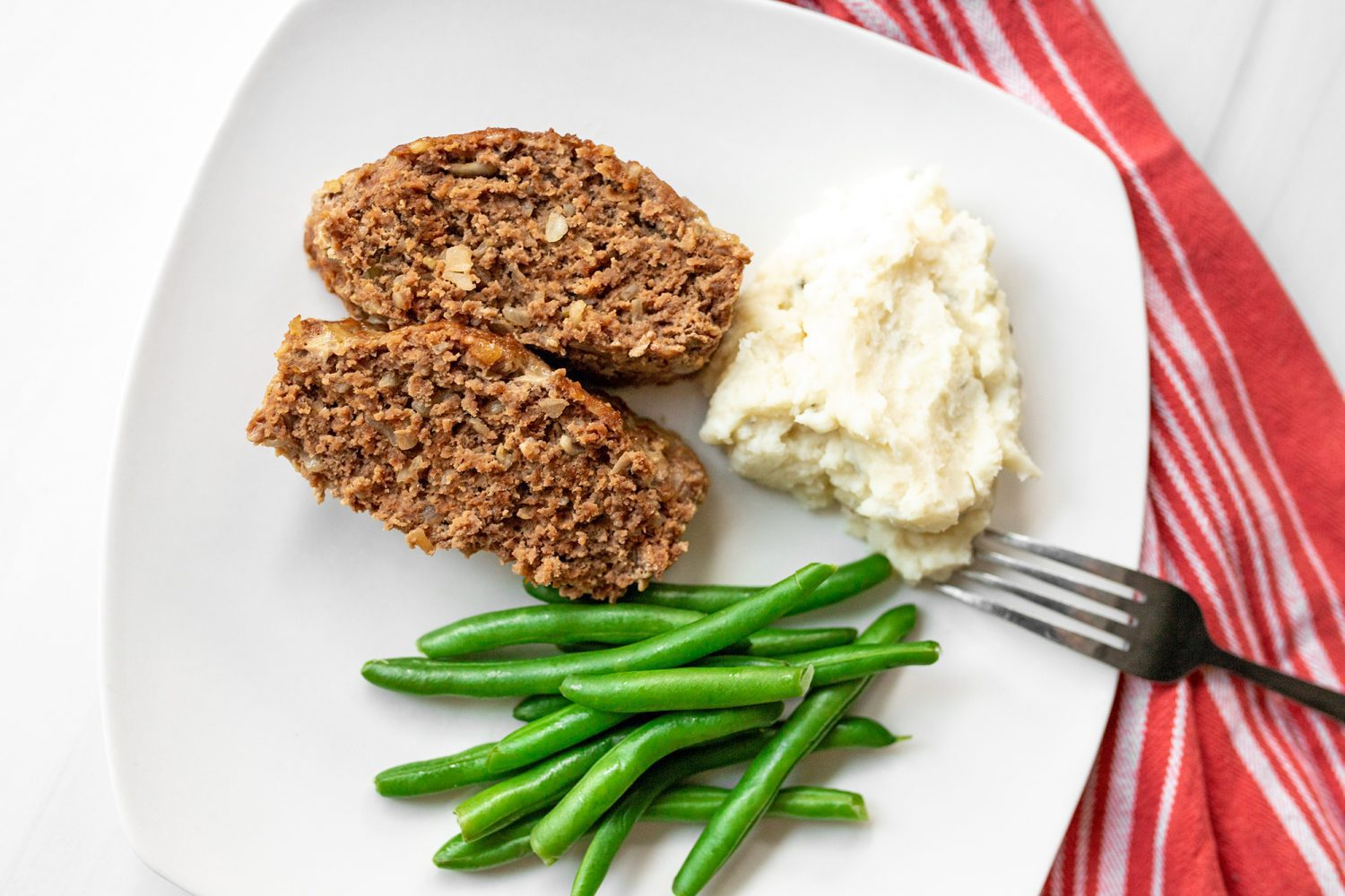 plate of meatloaf mashed potatoes and green beans