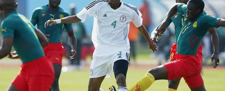 Super Eagles forward Kanu surrounded by Cameroon shirts
