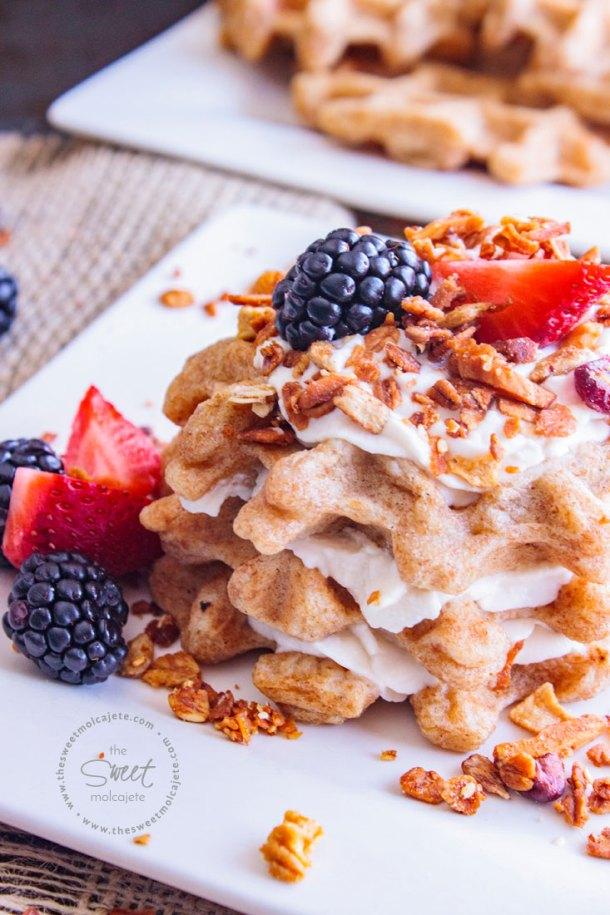 Acercamiento a un plato con 3 waffles integrales hechos sandwich con yogurt entre cada waffle y acompañados con fresas, zarzamoras y granola