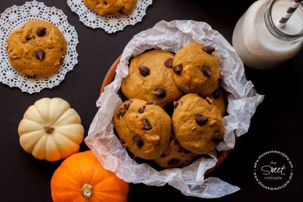Vista de arriba a un plato lleno de galletas de calabaza con chispas de chocolate, hay dos galletitas sobre la mesa, calabazas decorativas y un vaso de leche con popote en blanco y negro