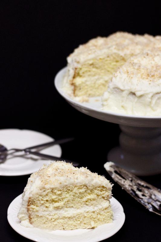 Acercamiento a una rebanada de pastel de tres leches con cobertura de coco, al fondo de ve el resto del pastel sobre un cake stand