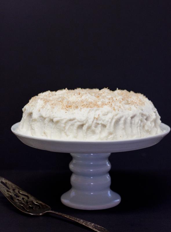 Pastel de Tres Leches de Coco sobre un pedestal de cerámica para pastel.