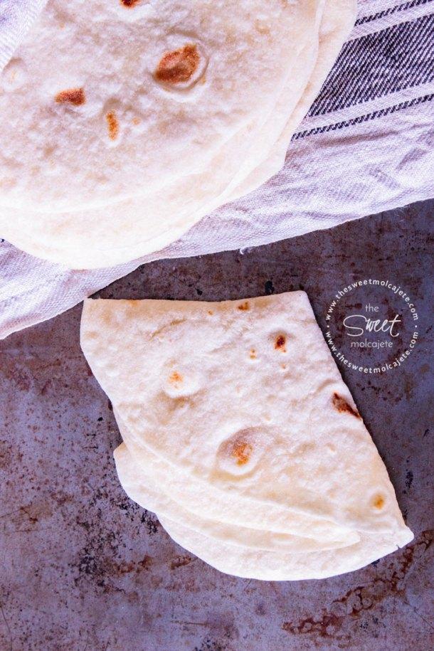Vista de arriba aun apilo de tortillas y una de ellas esta doblada en cuartos para mostrar lo suave que es