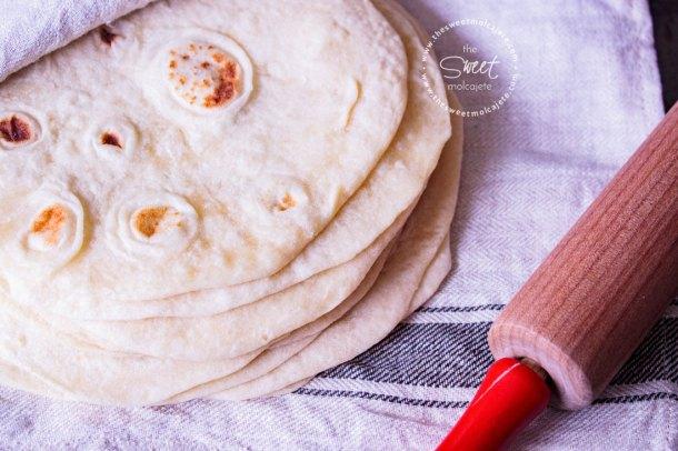 Acercamiento a un apilo de tortillas de harina obre una servilleta de lino