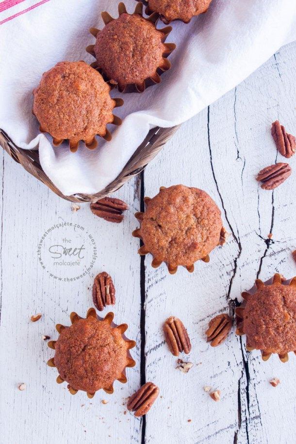 Vista de arriba de una canasta llena de muffins integrales de plátano, hay algunos muffins en la mesa y nueces alrededor