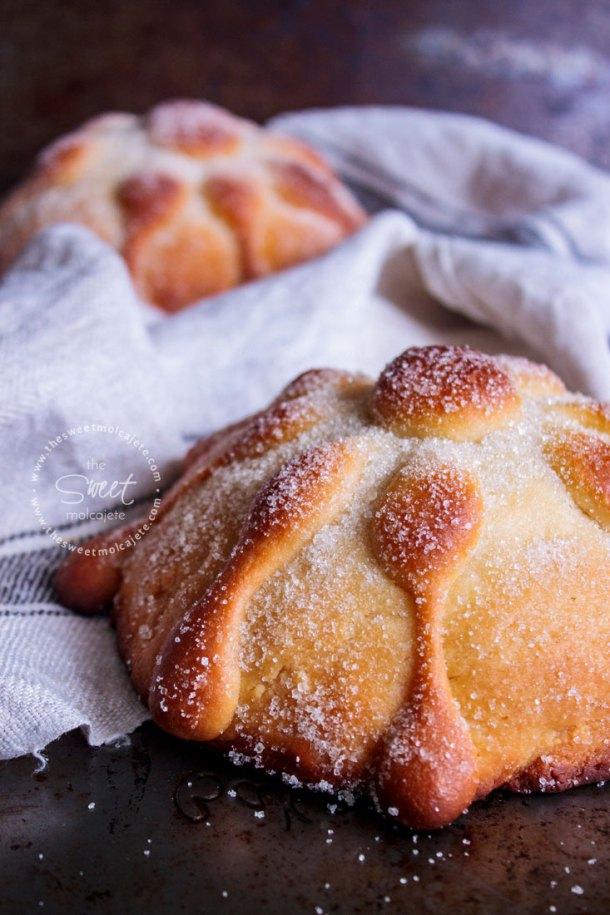 Acercamiento a un pan de muerto casero sobre una tela de lino, al fondo se ve otro pan