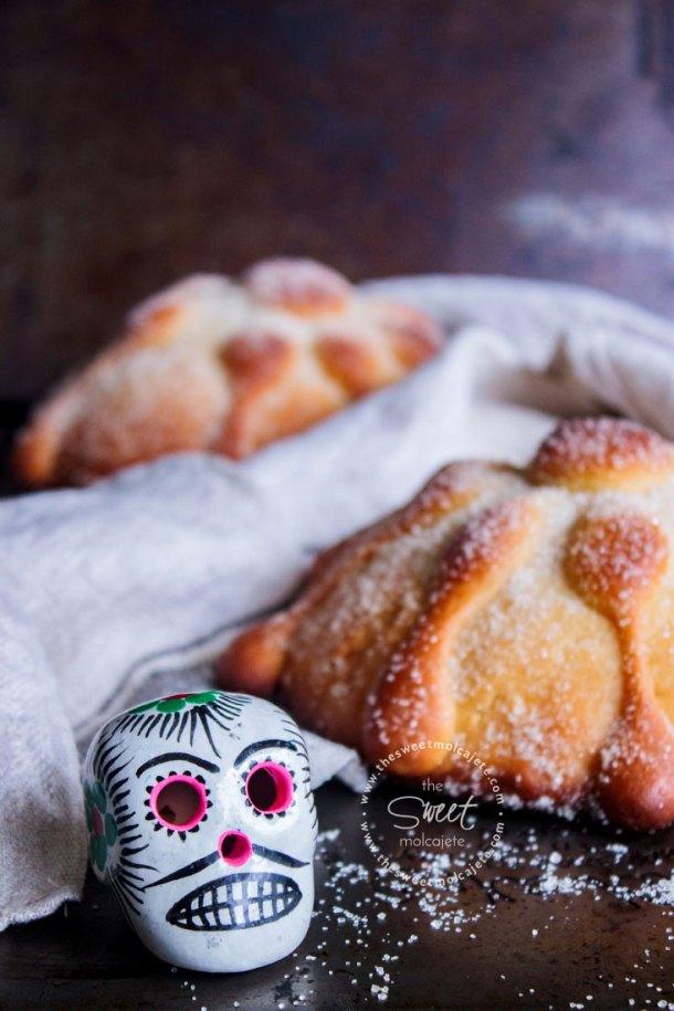 Calaverita de cerámica tradicional mexicana , al fondo se ven dos panes de muerto caseros