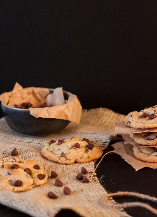 Mesa con varias galletas de chispas de chocolate y un plato con chocchips