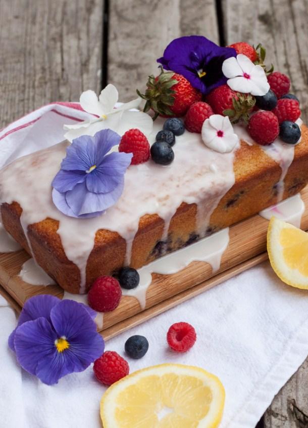 Panqué de limón decorado con glaseado, frutas frescas y flores comestibles
