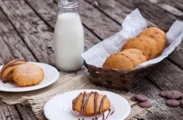 Fotografía de dos platos con Gorditas Dulces de Maíz. Las gorditas tienen chocolate derretido y una de ellas un poco de azúcar de caña espolvoreada encima. Al fondo se ve un frasco con leche y un canasto con más gorditas dulces