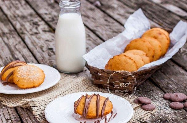 Gordita inflada dulce con chocolate derretido en un plato, al fondo maás gorditas de maíz en una canasta