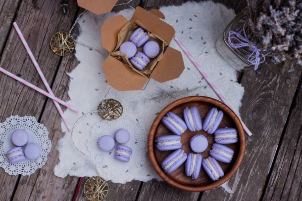 Mesa con varios macarons en plato de madera y cajitas de carton, hay luces y un florero