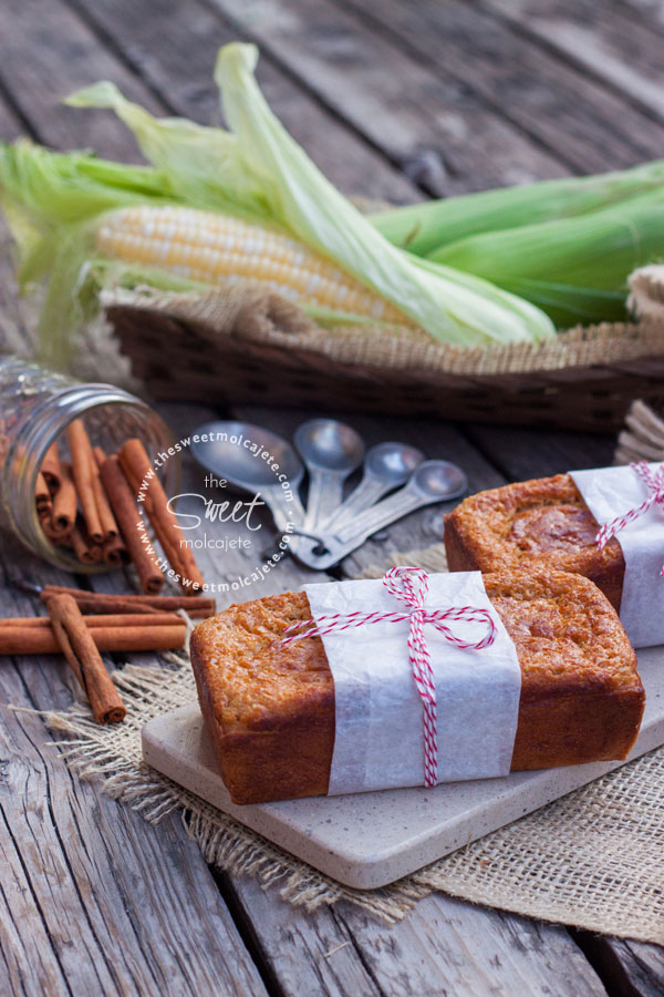 Dos barras de pan de elote envueltas con papel blanco y un lazo rojo por en medio, al fondo se ve una canasta con elote fresco y un frasco con rajas de canela