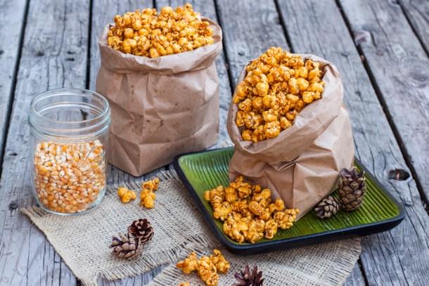 Dos bolsa de papel llenas Palomitas de Caramelo, un frasco con maíz palomero a un lado