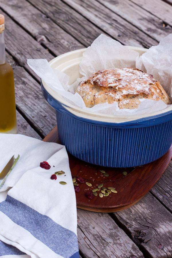 pan artesanal multigrano con corteza crujiente dentro de una olla de cerámica