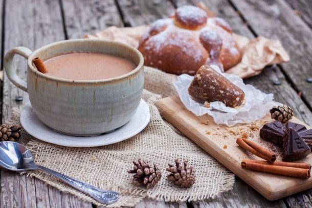 Mesa con un pan de muerto y una taza de champurrado, en una tablita hay piloncillo, canela y chocolate mexicano