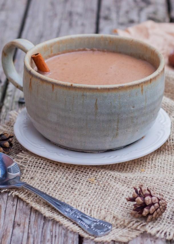 Acercamiento a una taza de champurrado con una rajita de canela