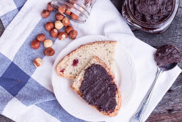 Vista de arriba a un plato con pan artesanal, una rebanada está untada con nutella casera