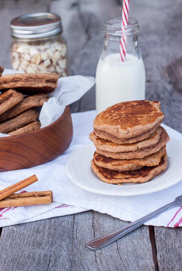 Mesa con hotcakes en un plato, un vaso con leche y un frasco con almendras