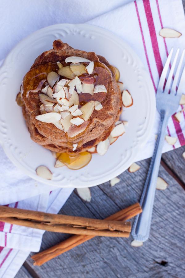 Vista de arriba a un plato con hotcakes integrales servidos con miel y almendras