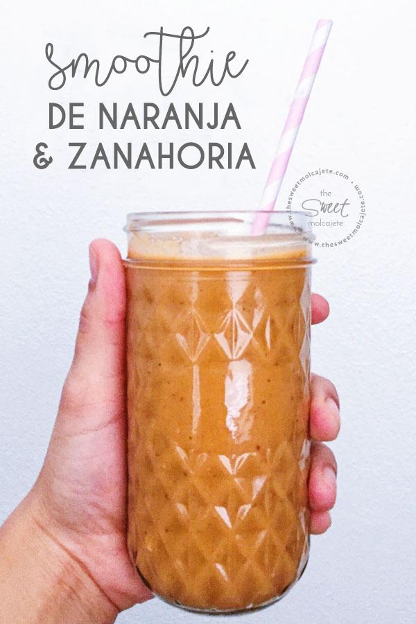 vaso de cristal con smoothie de naranja y zanahoria u un popote de papel