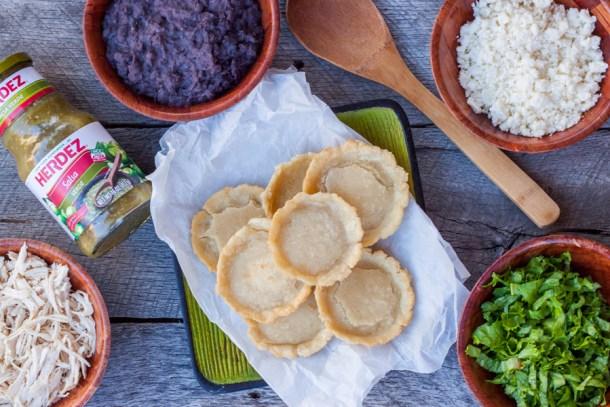 vista de arriba a un plato con sopes recién hechos y los platos con ingredientes para prepararlos