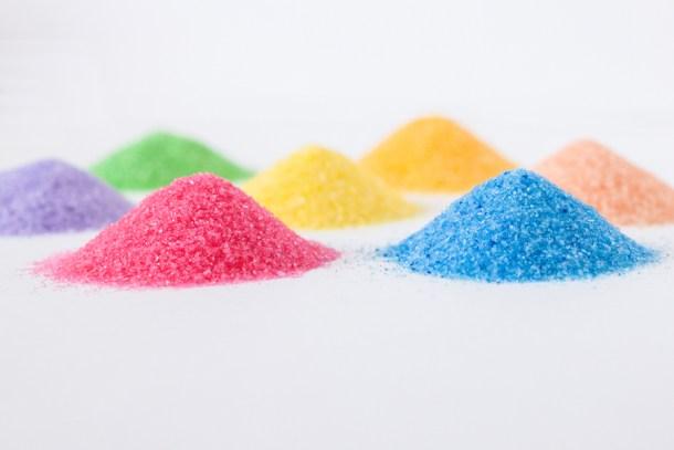 montoncitos de azúcar en 7 colores diferentes sobre una mesa blanca