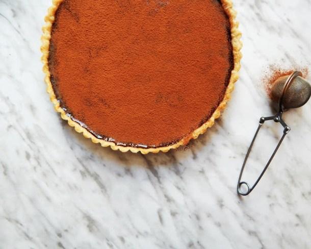 Tarta de Chocolate vista desde arriba con un cernidor pequeño con cocoa a lado