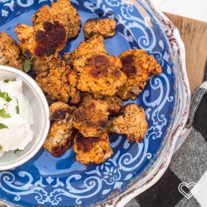 Plato con coliflor horneada a la paprika con un platito con ranch para acompañar a un lado para celebrar el Dia del Padre