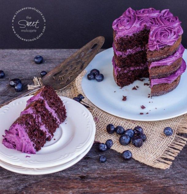 Pastelito de chocolate tipo naked cake con betun de moras con una rebanada en un plato para celebrar el Dia del Padre