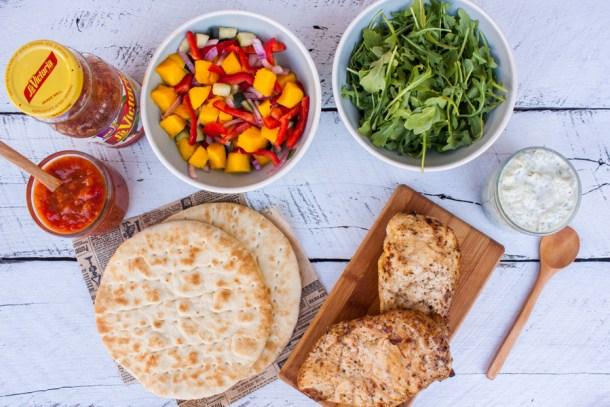 mesa con ingredientes para preparar unos gyros de pollo (salsa La Victoria, ensalada de mango, pollo, pan pita, salsa Tzatziki y arúgula)