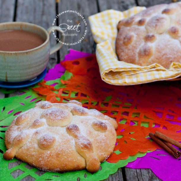 Pan de Muerto sobre una mesa de madera cubierta con papel picado y una taza de champurrado