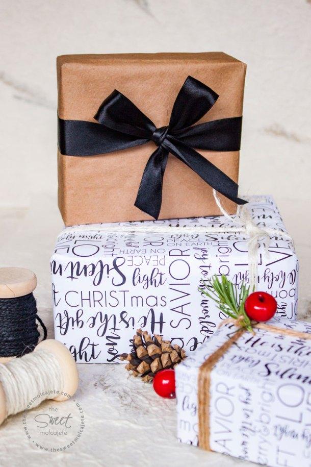 Regalos envueltos con una linda envoltura de regalos para Navidad con un diseño en blanco y negro. También hay un regalo encima de otro que está envuelto con papel craft café y con un lindo moño de listón negro.