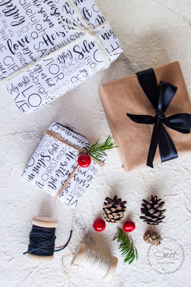 Vista aérea de 3 regalos navideños junto a otros objetos de navidad como piñas de pino, ramitas de pino y cordones rústicos. Dos de los regalos están envueltos con una linda envoltura de regalos para Navidad con un diseño en blanco y negro.