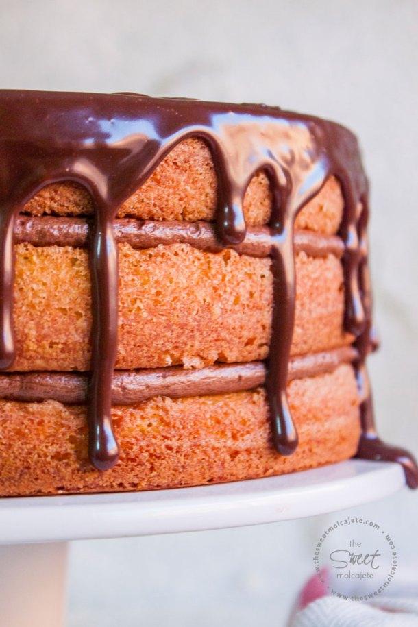 Acercamiento al pastel de mantequilla en tres capas relleno de un cremoso buttercream de chocolate y con un ganache de chocolate de cobertura que escurre por las orillas del pastel.