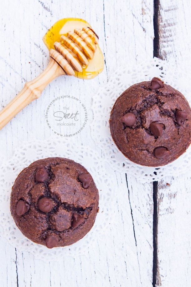 Vista aérea de dos Muffins de Chocolate sin gluten sobre una mesa de madera rústica blanca y con una palita mielera con miel escurriendo sobre la mesa