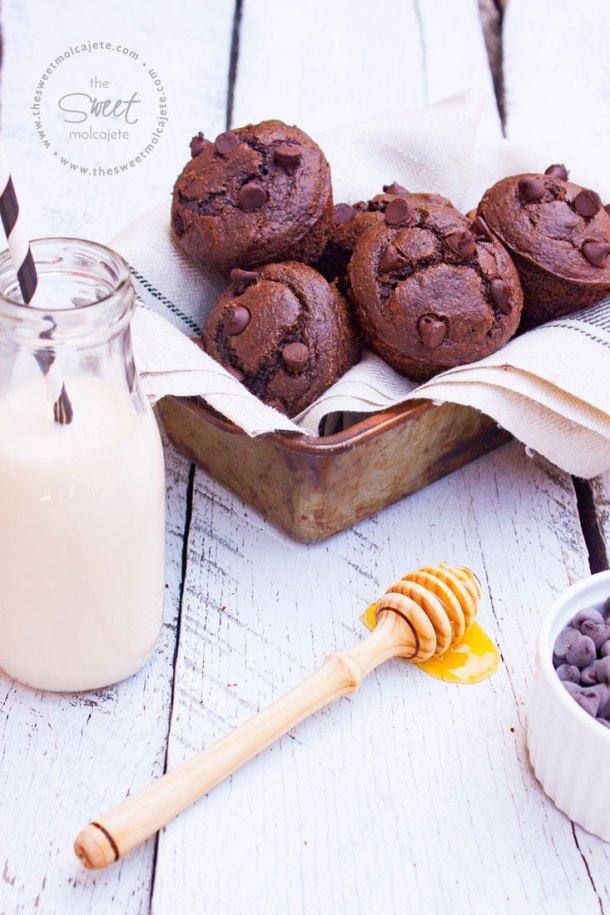 Muffins de Chocolate sin gluten acomodados en un molde metálico rústico cubierto con una tela de lino. Se ven una botellita con leche con popote, una palita mielera con miel escurriendo sobre la mesa