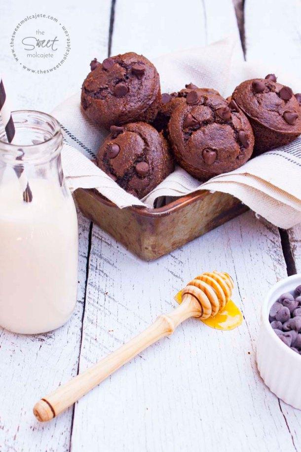 Muffins de Chocolate sin gluten acamodados en un molde metálico para pan avejentado cubierto con una telita en color beige. Se ven una botellita con leche y un popote, un palito mielero con miel escurriendo sobre la mesa y un ramekin lleno de chispas de chocolate.