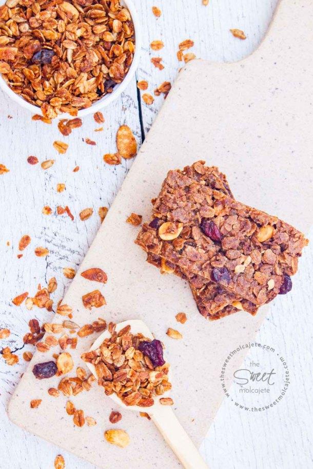 Vista aérea de Barritas de Granola Casera apiladas una sobre otra, hay una cuchara de madera con granola casera el frente de estas y un recipiente de cerámica blanco al fondo lleno de granola casera.