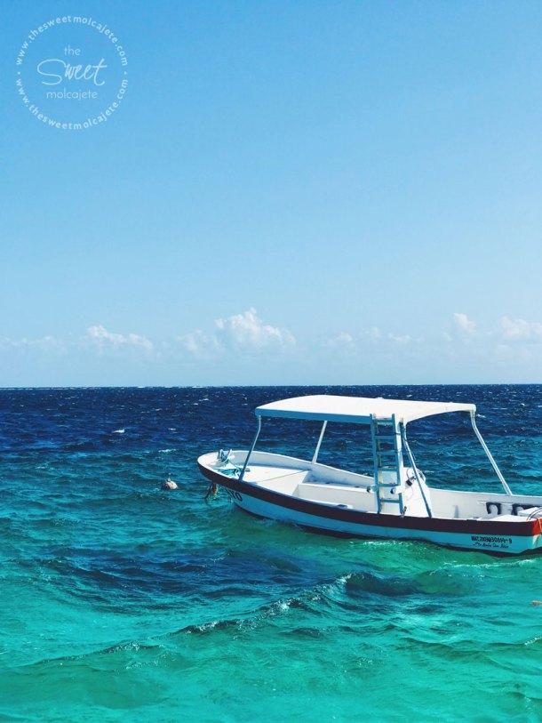 Fotografía de una lancha en el agua turquesa de la Riviera Maya - Vida Slow