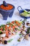 Tacos de Lengua en crockpot servidos con salsa, cebolla y cilantro y con varias cebollitas de cambray asadas. Al fondo un molcajete con salsa roja y una cazuelita con limones