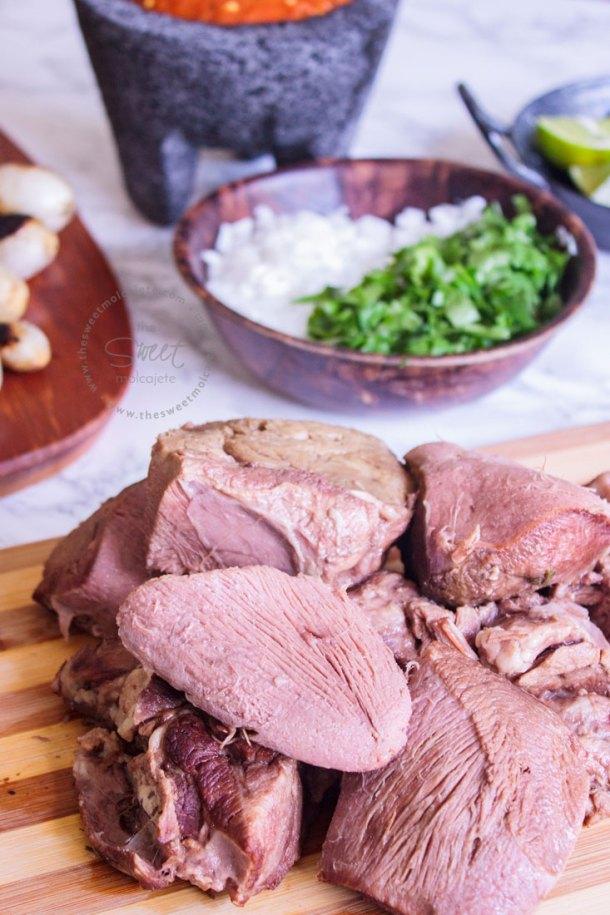 Trozos de Lengua de Res cocinada en crockpot ou olla de cocción lenta sobre una tabla para picar. Al fondo se ve un plato con cebolla y cilantro picados, cebollitas de cambray y un molcajete con salsa roja.