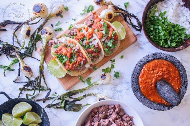 Tacos de Lengua en crockpot servidos con salsa, cebolla y cilantro y con varias cebollitas de cambray asadas alrededor. Se alcanza a ver alrededor un plato con cilantro picado, un molcejete con salsa roja, un plato con carne de lengua picada y limones.