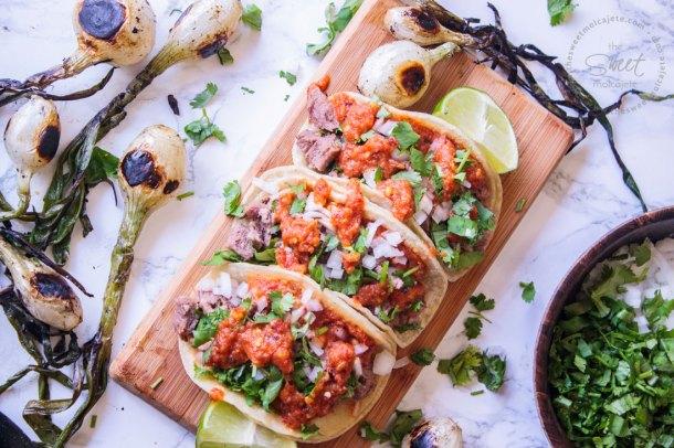 Tres tacos de lengua de res cocinado en crockpot servidos sobre una tablita de madera acompañados de cilantro, cebolla y salsa, con dos limones a los lados y cebollitas de cambray alrededor