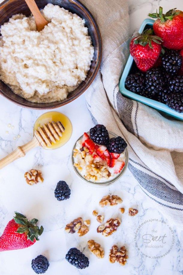 Vista aérea del Desayuno de Quinoa con Yogurt. Un bowl lleno de quinoa con yogurt y un crate de cerámica con fresas y zarzamoras. Hay nueces y berris en la mesa junto con una palita con miel.